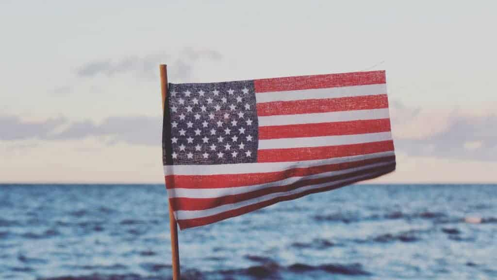 Image of a small American flag. In the background is the ocean.